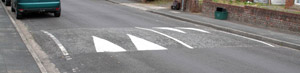 There are various ways that markings on the road can warn you of hazards and they are not all via paint, for example, road-hump markings: